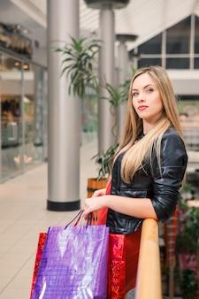 Mooie jonge vrouw met boodschappentassen in het winkelcentrum