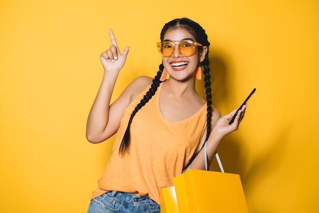 Mooie jonge vrouw met boodschappentassen met behulp van haar slimme telefoon op gele achtergrond.