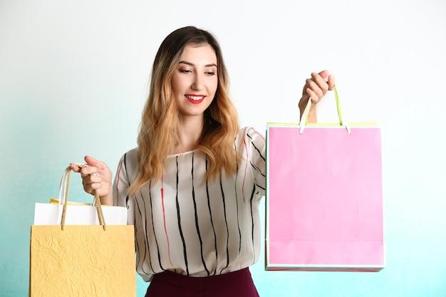 Mooie jonge vrouw met boodschappentassen op licht