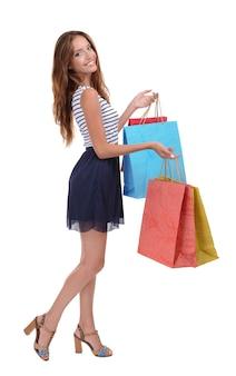 Mooie jonge vrouw met boodschappentassen op wit