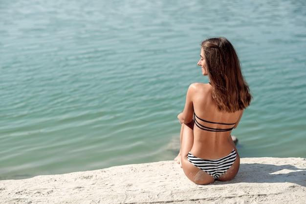 Mooie jonge vrouw met bruin haar in zwarte zwembroek op het strand. hete zomerdag op de