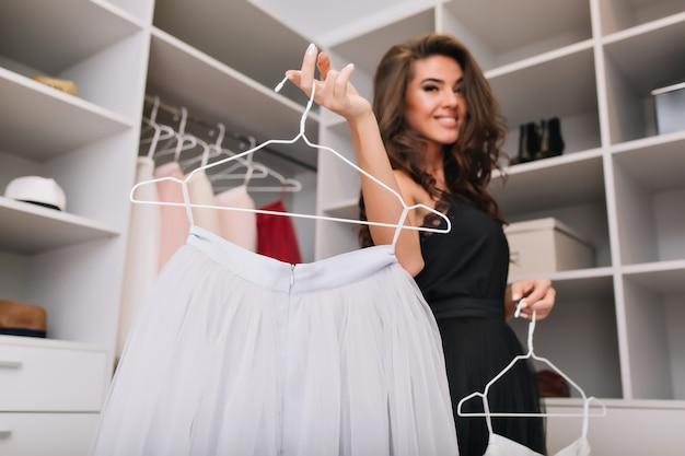 Mooie jonge vrouw met bruin krullend haar met witte mooie rok op hanger, blij om mooie kleren te hebben. luxe kledingkast. model met modieuze look, gekleed in zwarte elegante jurk.