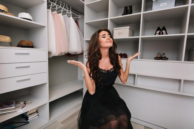 Mooie jonge vrouw met bruin krullend haar, zittend in kleedkamer, kledingkast, teleurgesteld, overstuur, moeilijk om een keuze te maken, niets om te dragen. model draagt zwarte kostuums, elegante uitstraling.