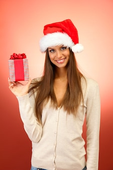 Mooie jonge vrouw met cadeau, op rode achtergrond