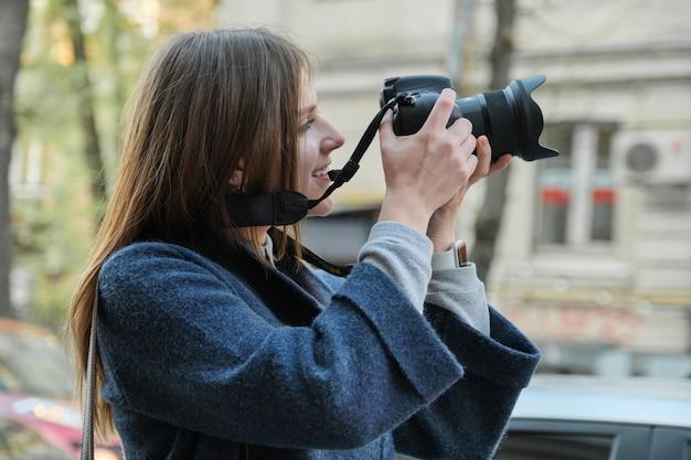 Mooie jonge vrouw met camera in stad.
