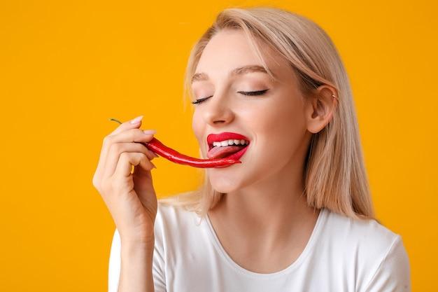 Mooie jonge vrouw met chili peper op kleur oppervlak