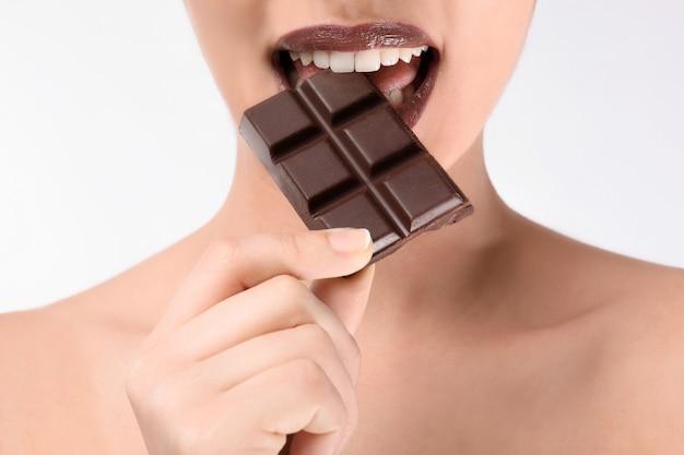 Mooie jonge vrouw met chocolade op witte ondergrond, close-up