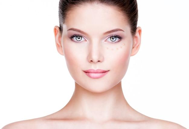 Mooie jonge vrouw met cosmetische foundation op een huid. schoonheidsbehandeling concept.