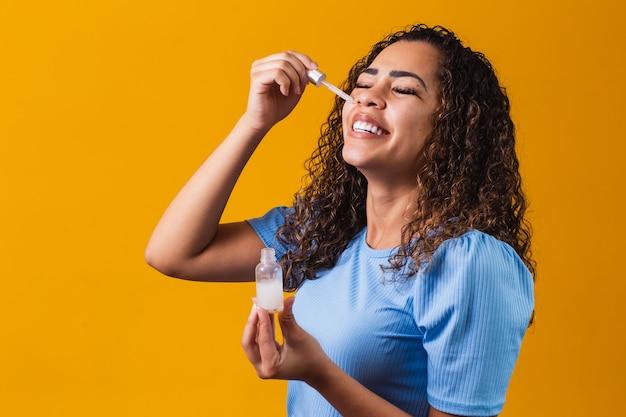 Mooie jonge vrouw met cosmetische olie op kleur achtergrond