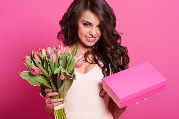 Mooie jonge vrouw met de lenteboeket en giftdoos