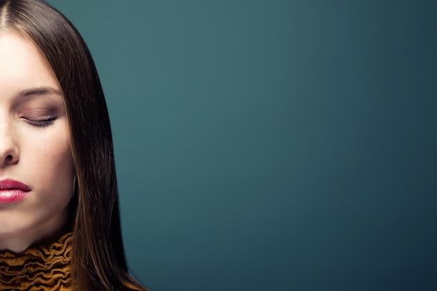 Mooie jonge vrouw met de ogen gesloten poseren geïsoleerd gedurende zwarte achtergrond.