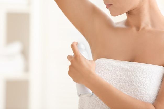 Mooie jonge vrouw met deodorant thuis