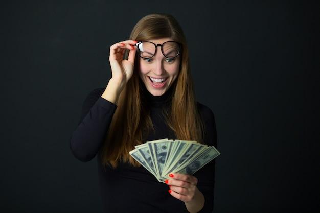Mooie jonge vrouw met dollars op zwarte achtergrond