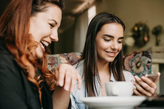 Mooie jonge vrouw met donker lang haar op zoek naar een smartphonescherm dat lacht terwijl haar vriend lacht tijdens het zingen in een café.