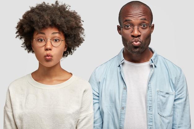 Mooie jonge vrouw met donkere huid heeft golvend haar, afro-amerikaanse man in denim overhemd, naast elkaar staan, ronde lippen, grimas trekken, geïsoleerd over witte muur. vriendschap concept