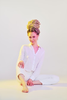 Mooie jonge vrouw met dreadlocks in witte kleren zit op de vloer in lichte studio