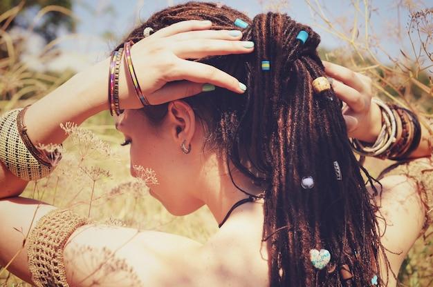 Mooie jonge vrouw met dreadlocks kapsel verzameld in een paardenstaart en versierde diverse kralen