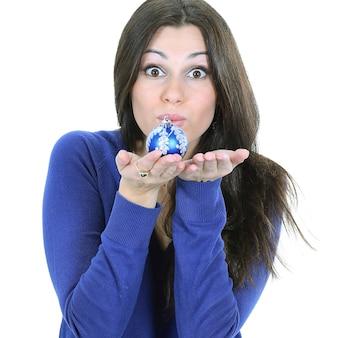 Mooie jonge vrouw met een blauwe kerstbal. geïsoleerd op een witte muur