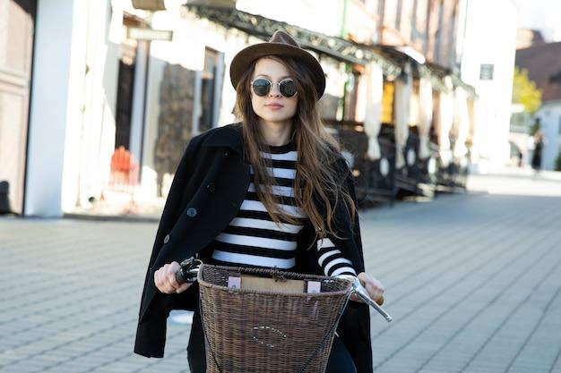 Mooie jonge vrouw met een fiets in de stad. milieutransport