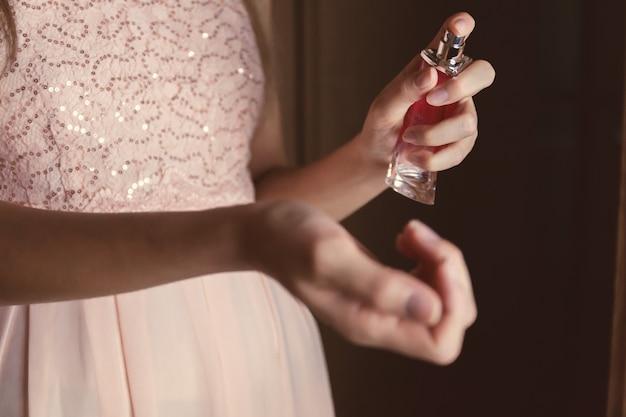Mooie jonge vrouw met een fles parfum thuis. detailopname