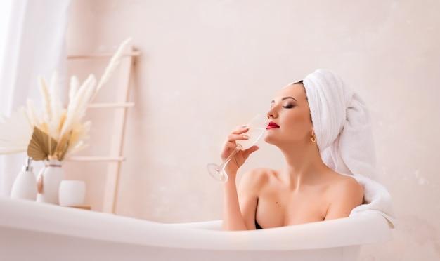 Mooie jonge vrouw met een glas champagne in de badkamer. een meisje met een handdoek over haar hoofd ligt in de badkamer. het concept van recreatie en schoonheidssalon.