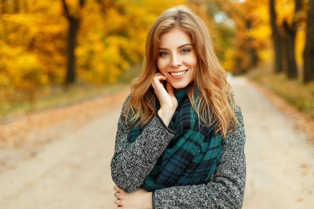 Mooie jonge vrouw met een glimlach die van het de herfstweer geniet in een park dichtbij het gele gebladerte