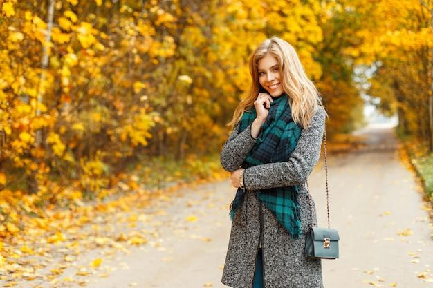 Mooie jonge vrouw met een glimlach in stijlvolle kleding in een herfst park van geel gebladerte
