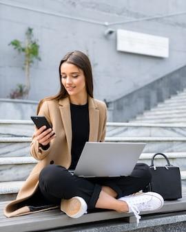 Mooie jonge vrouw met een herfstjas die een laptop gebruikt terwijl ze op een bank zit en een mobiele telefoon gebruikt
