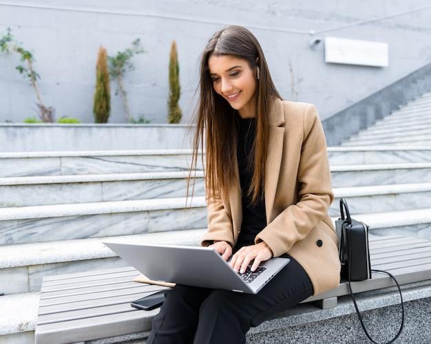 Mooie jonge vrouw met een herfstjas die een laptop gebruikt terwijl ze op een bank zit