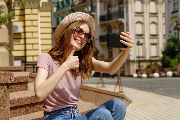 Mooie jonge vrouw met een hoed die een selfie neemt