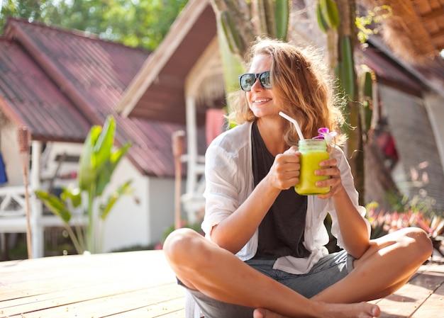 Mooie jonge vrouw met een in hand cocktail bij tropische toevlucht