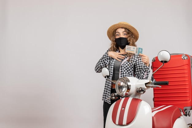 Mooie jonge vrouw met een kaartje in de buurt van de rode koffer van de bromfiets