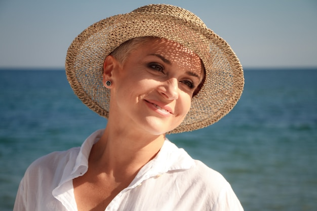 Mooie jonge vrouw met een kort kapsel in een strandhoed op het strand
