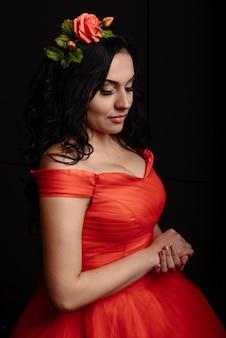 Mooie jonge vrouw met een krans van rozen in een luxe rode avondjurk op een zwarte
