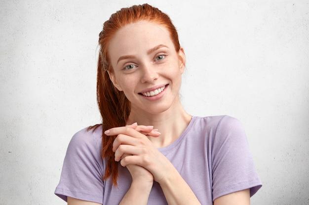 Mooie jonge vrouw met een prettige uitstraling, heeft een positieve uitdrukking, voelt zich tevreden als een prettig gesprek met een vriend, lacht zachtjes, heeft rood haar