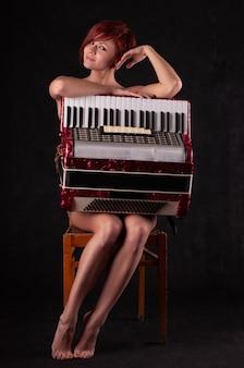 Mooie jonge vrouw met een rode accordeon poseren zittend op een stoel
