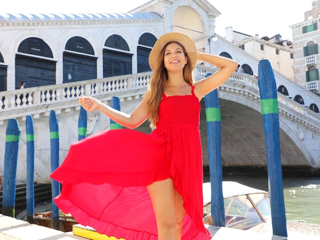 Mooie jonge vrouw met een rode jurk staat voor de beroemde rialtobrug in venetië, italië