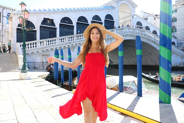 Mooie jonge vrouw met een rode jurk wandelen in venetië in de buurt van de rialtobrug, italië