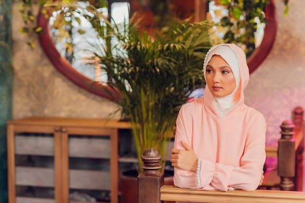 Mooie jonge vrouw met een roze hijab.