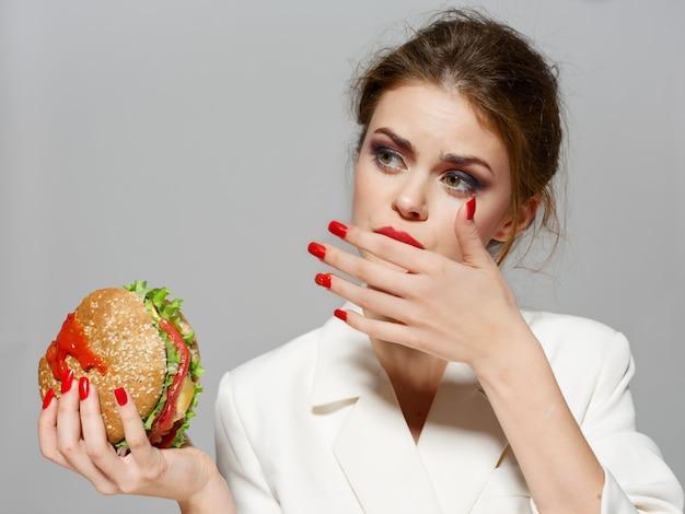 Mooie jonge vrouw met een sappige hamburger in haar handen, een vrouw die een hamburger eet