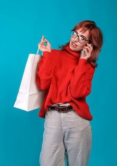 Mooie jonge vrouw met een witte blanco papieren zak en maakt aankopen in een online winkel tegen