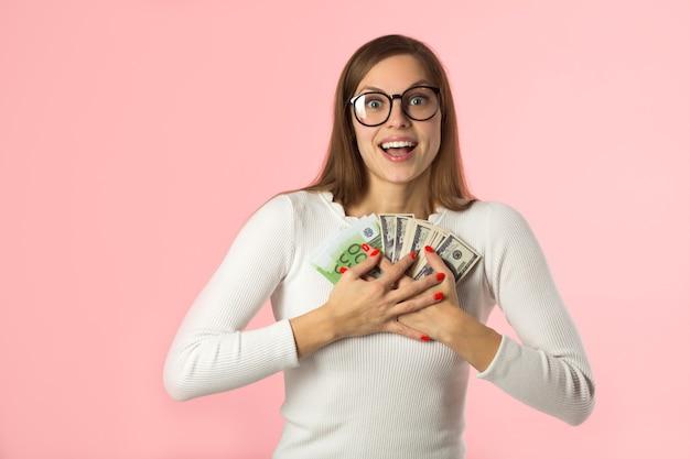 Mooie jonge vrouw met euro en dollars op roze achtergrond
