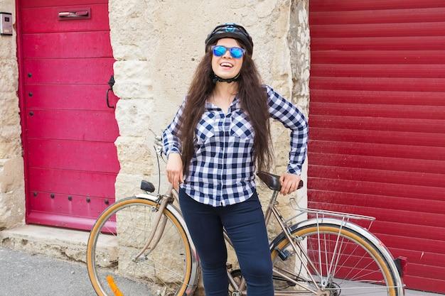 Mooie jonge vrouw met fiets en helm in straat op zonnige dag.