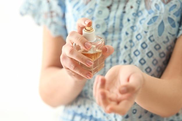 Mooie jonge vrouw met fles parfum op lichte achtergrond, close-up