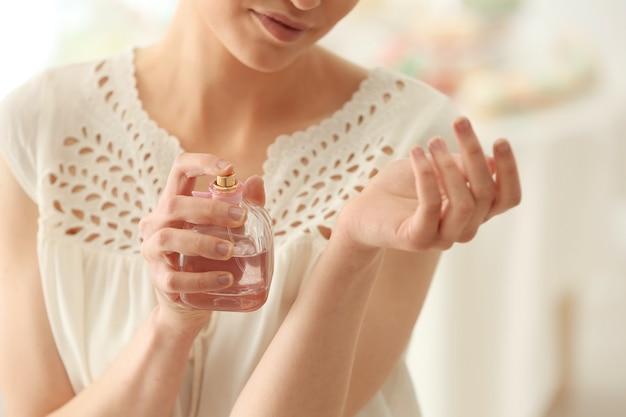 Mooie jonge vrouw met fles parfum thuis, close-up