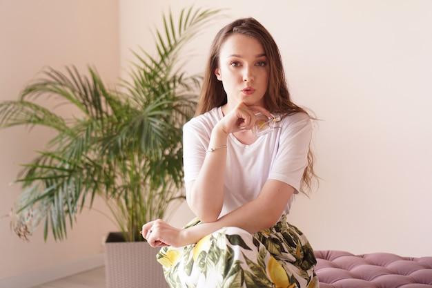 Mooie jonge vrouw met fles parfum thuis - roze kleedkamer