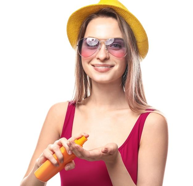 Mooie jonge vrouw met fles zonnebrandcrème op wit