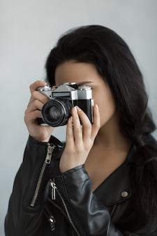 Mooie jonge vrouw met fotocamera binnenshuis. close-up portret van hipster stijlvolle jongeren