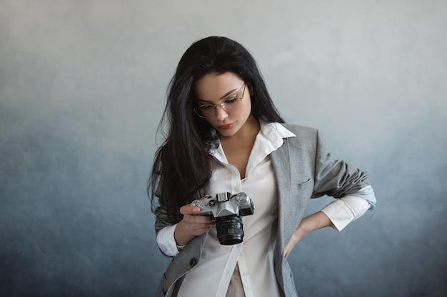 Mooie jonge vrouw met fotocamera binnenshuis. portret van modieus jong fotograafmeisje