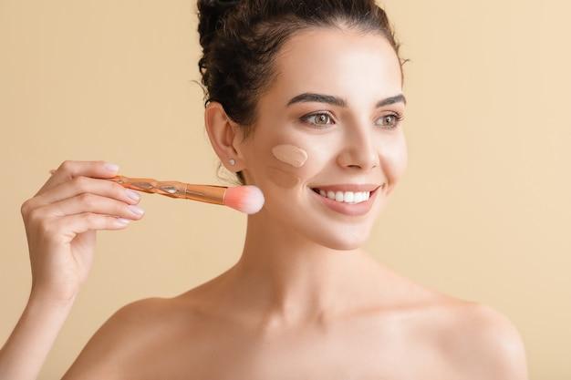 Mooie jonge vrouw met foundation op haar gezicht op beige